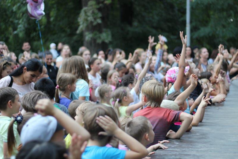 Porción de niños en la fiesta aumentar sus manos a la etapa Rusia, Saratov - agosto de 2019 imágenes de archivo libres de regalías
