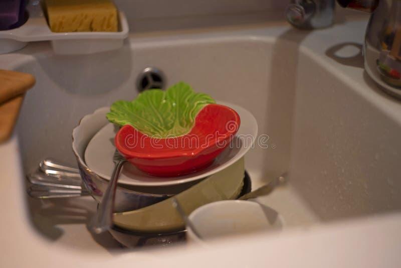 Porción de platos sucios en el fregadero blanco en la cocina imagen de archivo