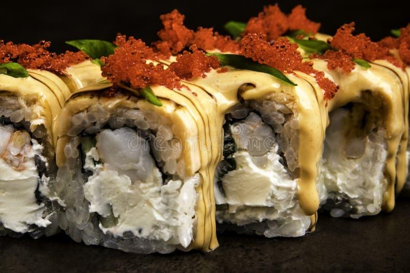 Porción de rollos con el caviar del tobiko en estilo japonés en un cierre oscuro del fondo para arriba fotos de archivo
