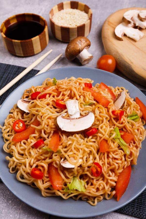 Porción de tallarines con los tomates, pimientas y setas, en una tabla de la porción Primer fotografía de archivo
