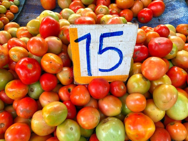 Porción de venta del tomate en mercado local fotos de archivo libres de regalías