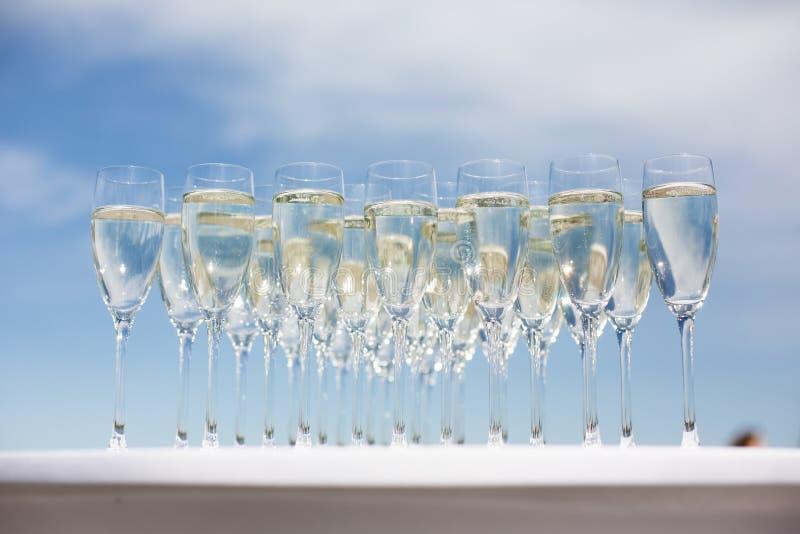 Porción de vidrios con champán en una tabla afuera imagen de archivo