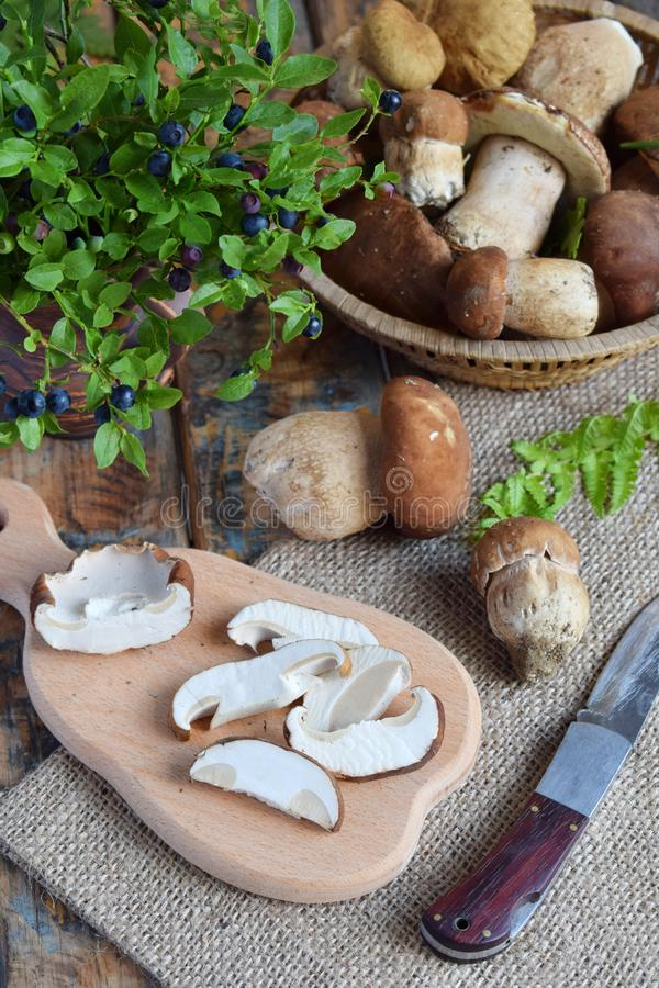 Porcini. Chopped white mushroom on wooden cutting board. Edible wild mushrooms. Food preparation. Summer or Autumn harvest. Copy stock images