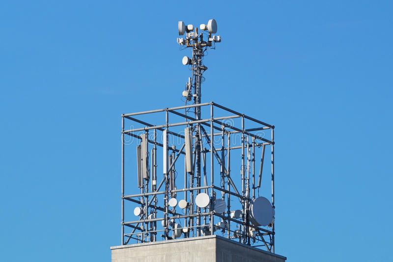 Porciones de antenas del telcommunication en el tejado una casa imagenes de archivo