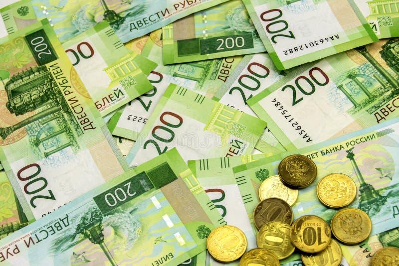Porciones de cuentas dispersadas en la tabla Billetes de banco digno de 200 rublos rusas Efectivo y algunas monedas imágenes de archivo libres de regalías
