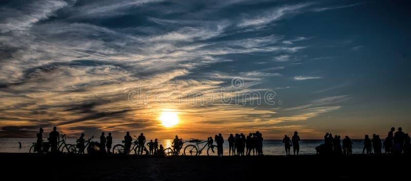Porciones de diversas actividades en la playa durante la puesta del sol foto de archivo