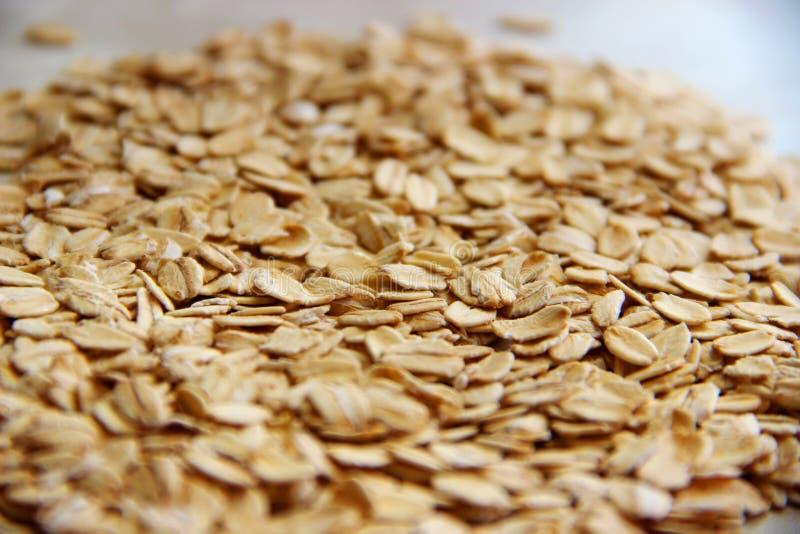 Porciones de escamas de la harina de avena o de la avena como fondo La avena útil forma escamas gluten libre imágenes de archivo libres de regalías