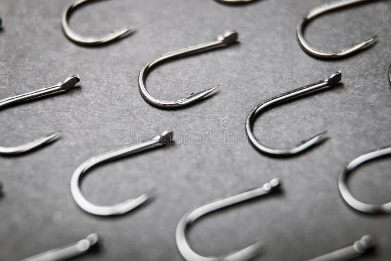 Porciones de ganchos de pesca en fondo negro imagenes de archivo