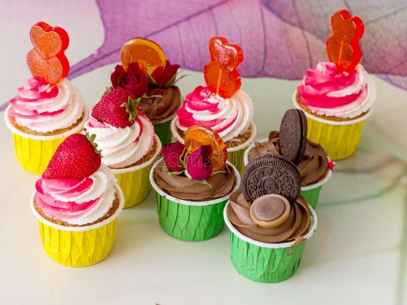 Porciones de magdalenas del chocolate, de la fresa y del caramelo foto de archivo