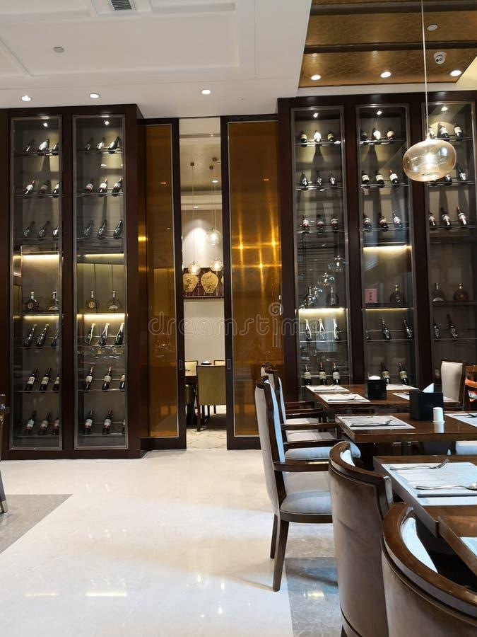 Porciones de vino y de su gabinete en el cuarto dinning en hotel imagenes de archivo