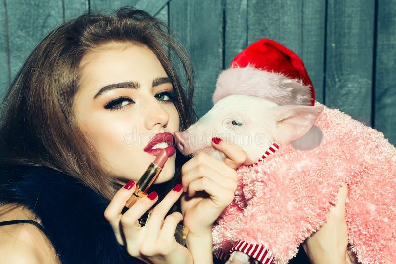 Porco afortunado Ano novo chinês Venda do ano 2019 novo no cosmético chinês Mulher com o porco do bebê com chapéu do Natal 2019 n imagem de stock