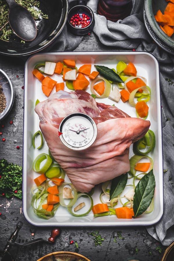 Porco assado que cozinha a preparação na tentativa do cozimento com vegetais e o temporizador da grade no fundo rústico da mesa d imagem de stock