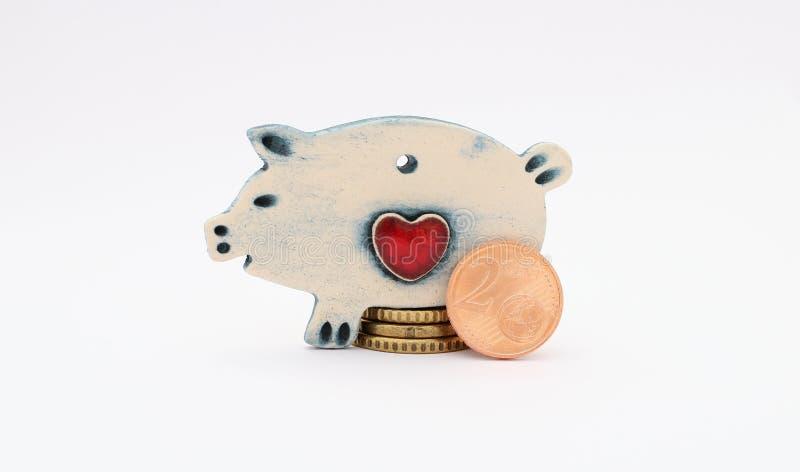 Porco cerâmico com as euro- moedas no fundo branco saving imagens de stock royalty free