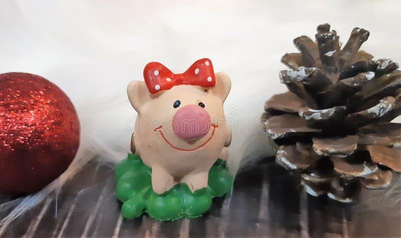 Porco do brinquedo e decoração do inverno, felicitações no feriado Símbolo do ano do porco no fundo de luzes de Natal fotografia de stock