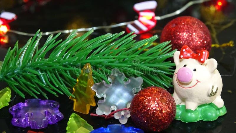 Porco do brinquedo e decoração do inverno, felicitações no feriado Símbolo do ano do porco no fundo do Natal fotografia de stock