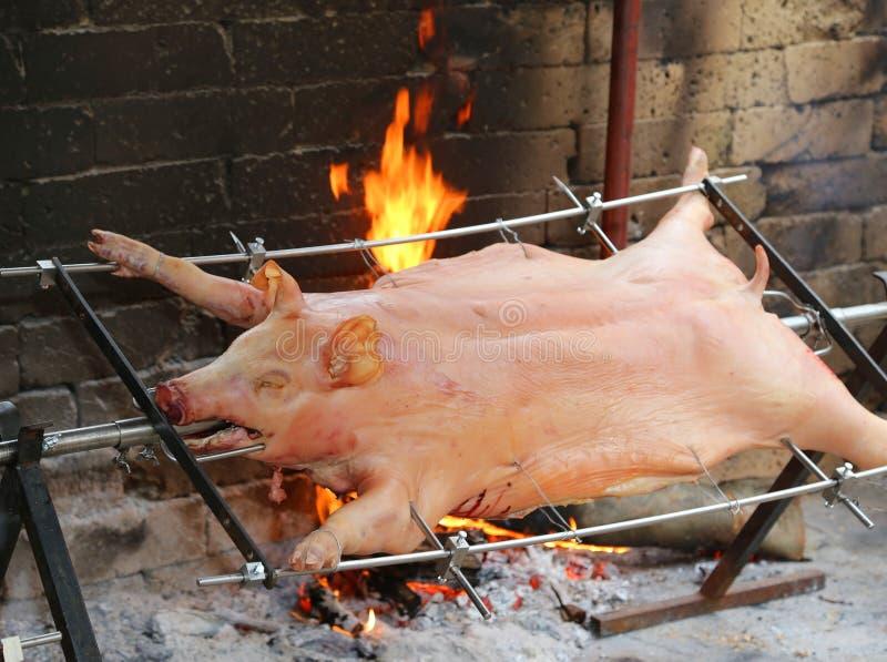 porco grande no cuspe e cozinhado lentamente na grande chaminé fotografia de stock royalty free