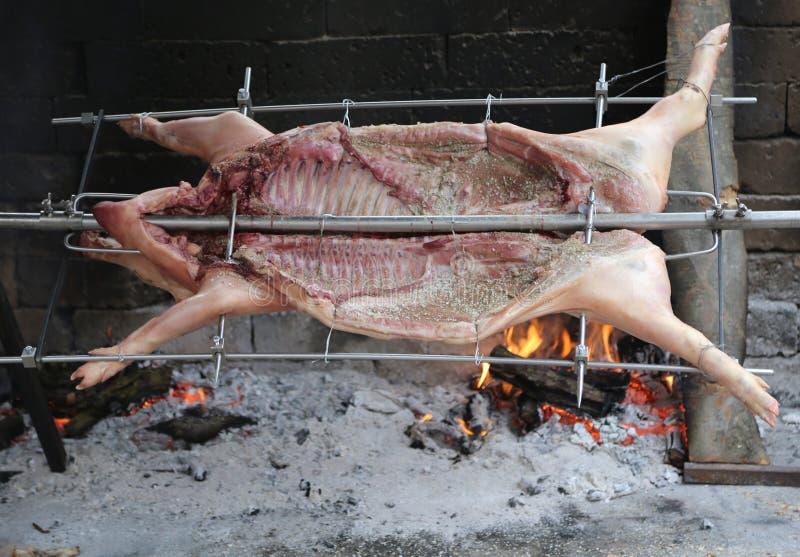 porco no cuspe e cozinhado lentamente na grande chaminé durante foto de stock