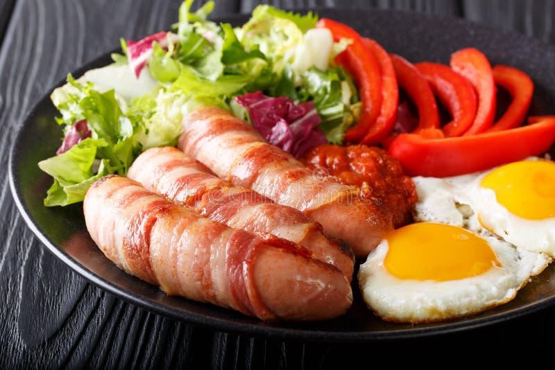 Porcos do café da manhã nas salsichas fritadas coberturas envolvidas no bacon, ovos fotografia de stock royalty free
