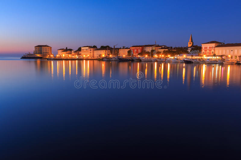 Poreč after sunset at dusk, Croatia. Poreč city lights reflecting in water after sunset at dusk, Croatia stock photo