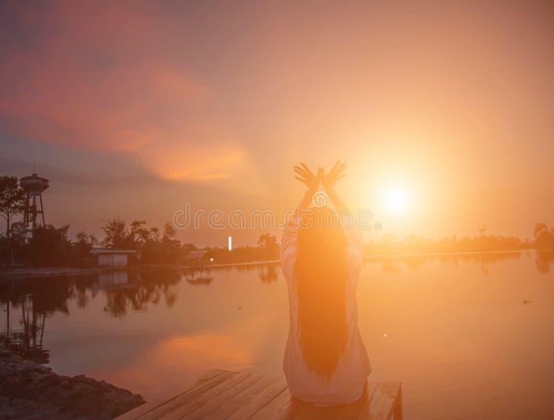 Pores do sol das mãos da jovem mulher da silhueta imagens de stock royalty free