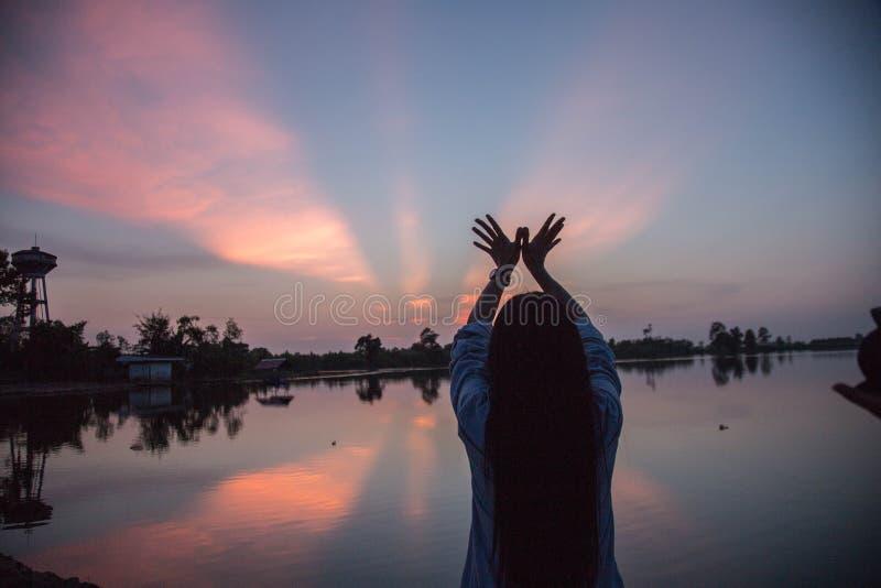 Pores do sol das mãos da jovem mulher da silhueta fotos de stock