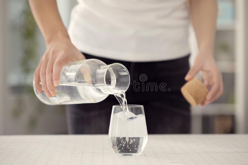Poring vatten för ung kvinna från flaskan till exponeringsglas royaltyfria foton