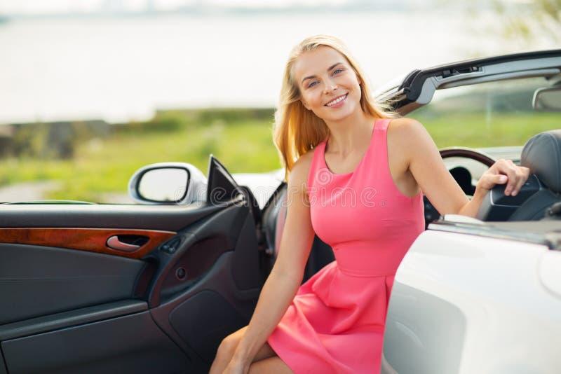 Porisng feliz de la mujer joven en coche convertible imagenes de archivo