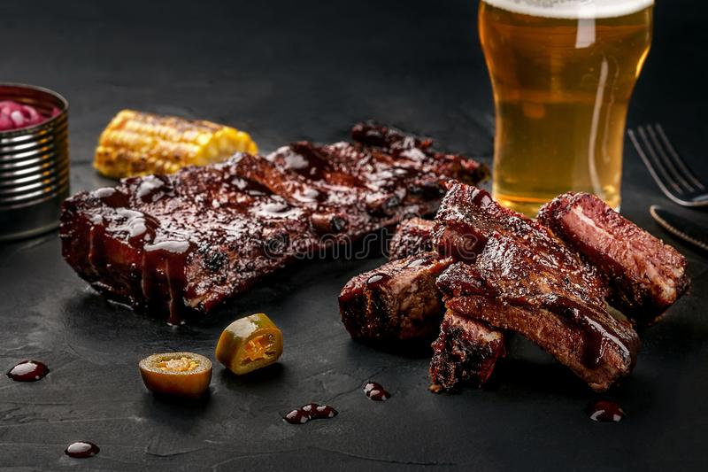 Pork ribs in barbecue sauce and a glass of beer on a black slate dish. A great snack to beer on a dark stone background. Pork and beef ribs in barbecue sauce and stock image