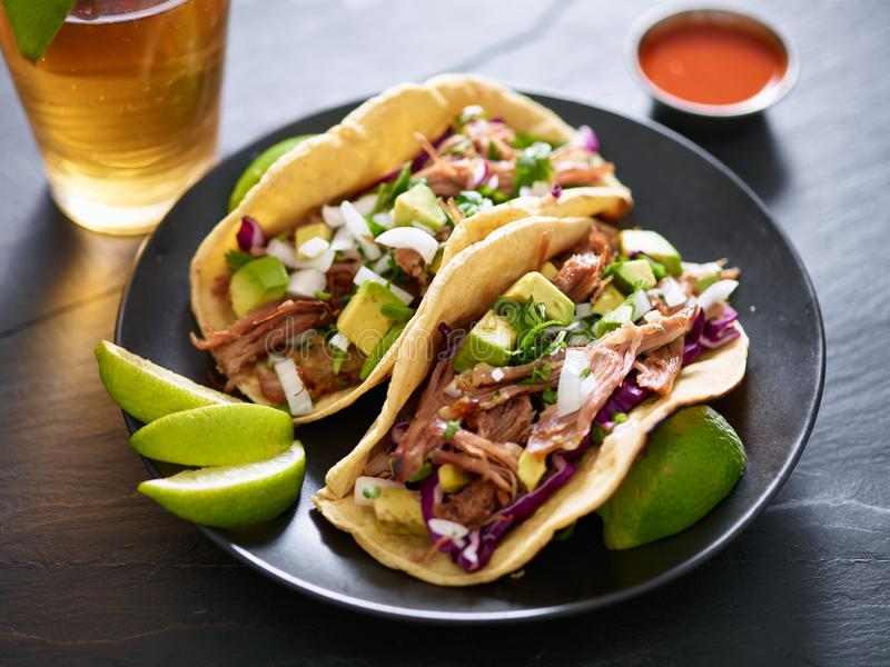 Pork carnita tacos close up with lime wedges and red cabbage royalty free stock photography