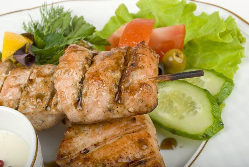 Pork (or chicken) on grill spit with salad. Pork (or chicken) on a grill spit with salad stock images