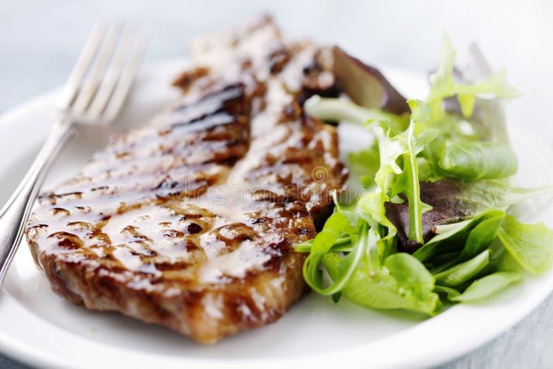 Pork chop. Juicy grilled pork chop (neck cut) with greens stock photo