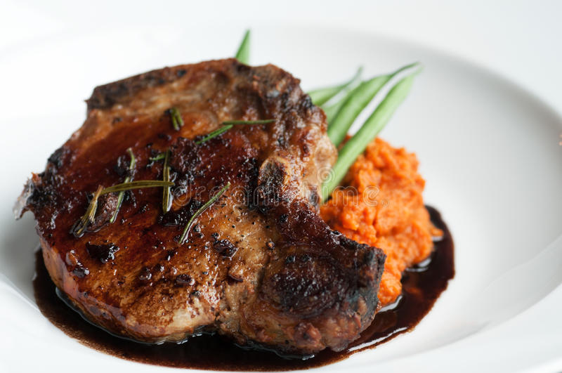 Pork Chop. Beautifully roasted pork chop with green beans and sweet potato puree stock photo