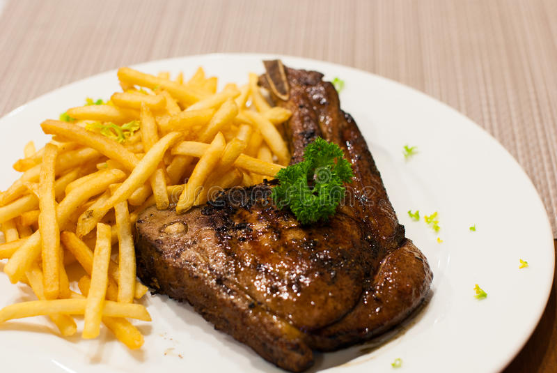 Pork Chop Grilled steak with French Fries, top with parsley. Pork Chop Grilled steak with French Fries, top with parsley at restaurants royalty free stock images