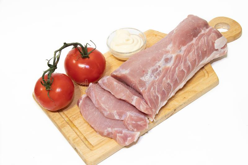 Pork chop isolated on white background. Meat on a white background. Raw meat and red tomatoes. Tomatoes on the branch royalty free stock photo