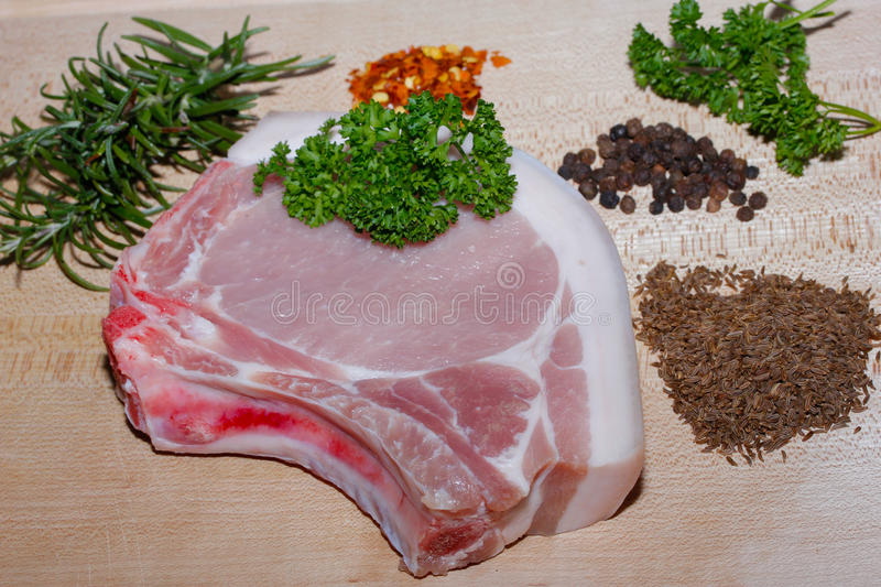 Pork Chop. Raw pork chop with spices and herbs on a wooden board stock photography