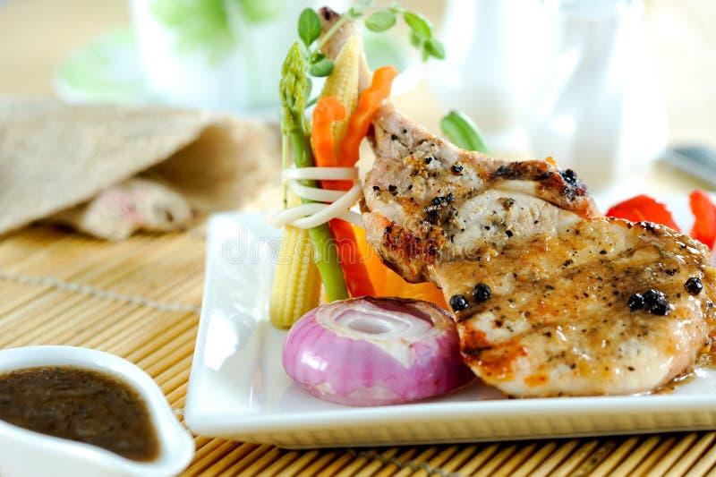 Pork chop steak. Serve with vegetable in restaurant royalty free stock photo