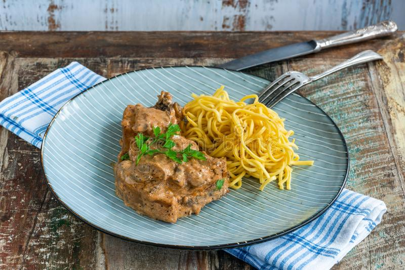 Pork chops in creamy cajun sauce with button mushrooms and egg noodles stock photo