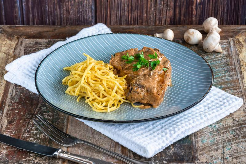Pork chops in creamy cajun sauce with button mushrooms and egg noodles royalty free stock photo