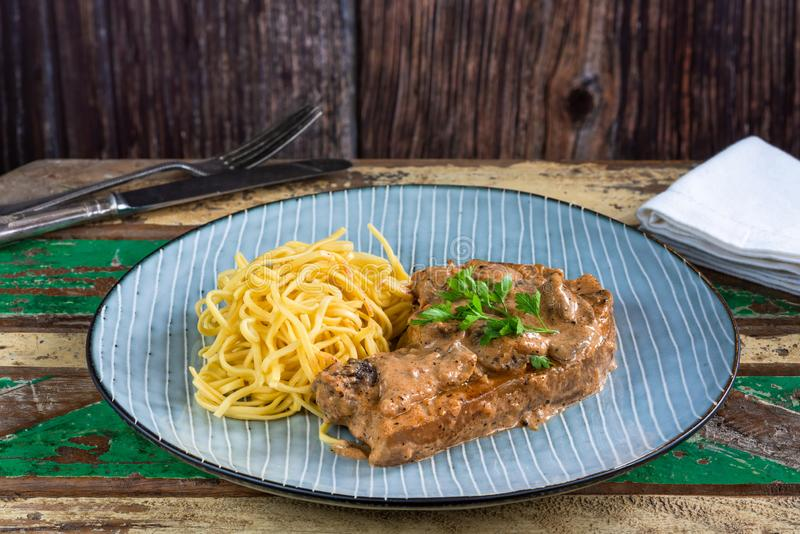 Pork chops in creamy cajun sauce with button mushrooms and egg noodles stock image