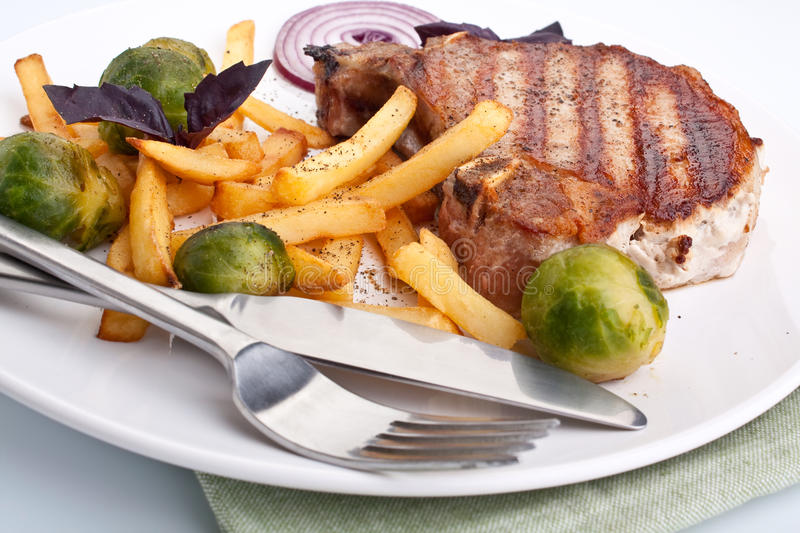 Pork chops with fries and brussels sprouts royalty free stock photo