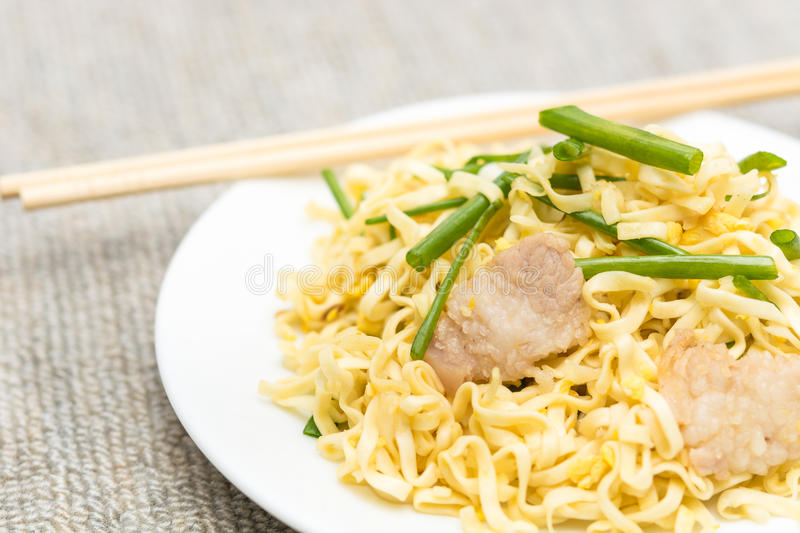 Pork chow mein. With chopsticks in white plate royalty free stock images