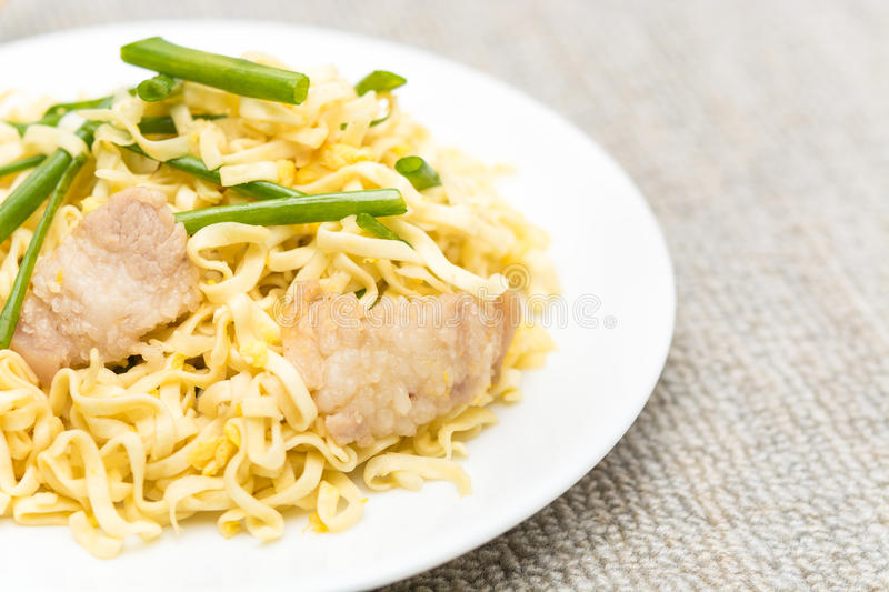Pork chow mein. With chopsticks in white plate stock images