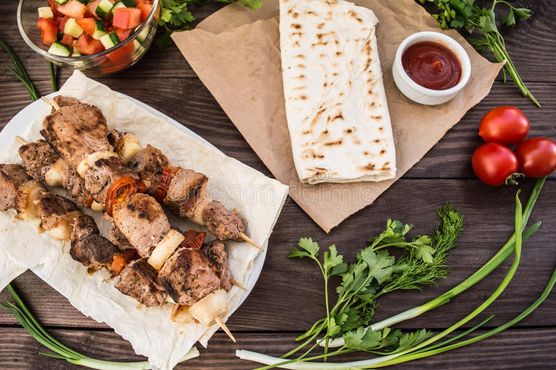 Pork cooked with vegetables on skewers a wooden background. Pork cooked with vegetables on skewers on a wooden table stock photo