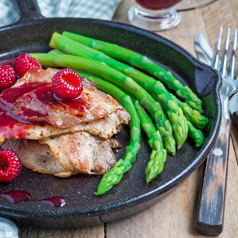 Pork cutlets with raspberry sauce and asparagus in iron cast pan, square royalty free stock photography
