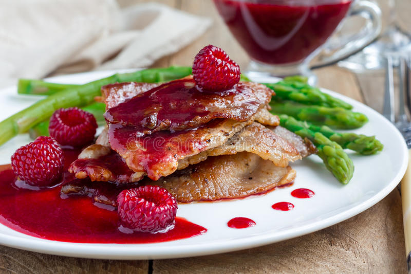 Pork cutlets with raspberry sauce and asparagus on white plate royalty free stock photo