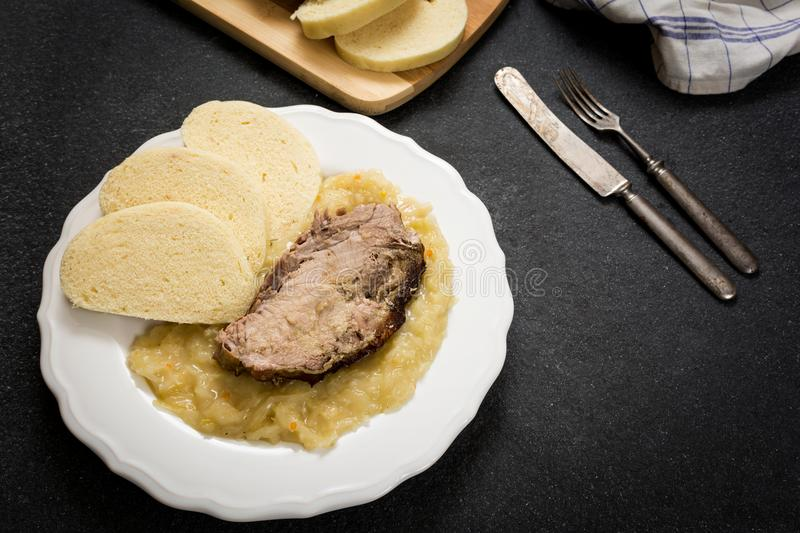 Pork dumplings and cabbage. Traditional czech cuisine pork meat, dumpings and cabbage on dark stone table stock photography