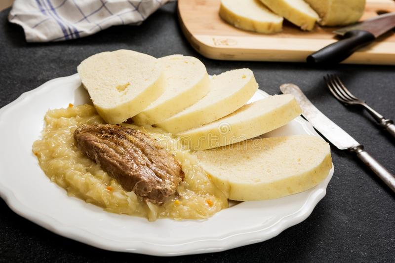 Pork dumplings and cabbage. Traditional czech cuisine pork meat, dumpings and cabbage on dark stone table stock images