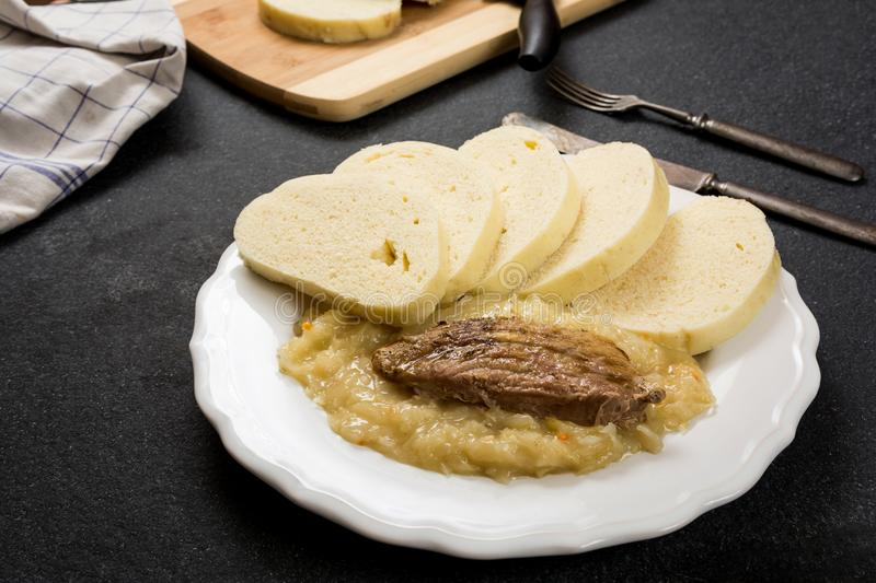 Pork dumplings and cabbage. Traditional czech cuisine pork meat, dumpings and cabbage on dark stone table stock photos