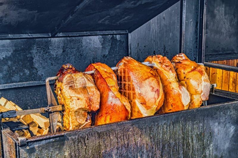 Pork ham meat is roasted on an open fire in the grill. Street Czech food. Prague, Czech Republic. stock photos