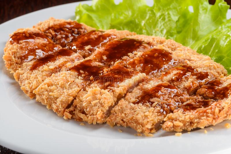 Pork in Japanese breading. With Tonkatsu sauce in macro of the camera. Tasty meat on the leaf of lettuce royalty free stock image
